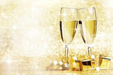 Two champagne glasses, gifts and decoration on golden background photo