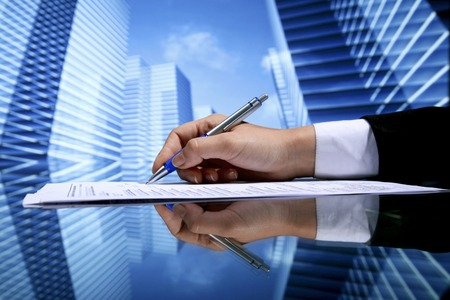 legal office: Realtor signing contract on skyscrapers background Stock Photo