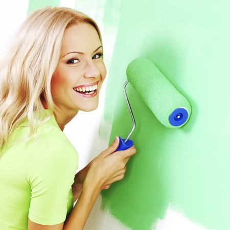 Smiling young woman painting the wall with roller brush photo