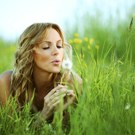 Young woman makes a wish blowing on dandelion photo