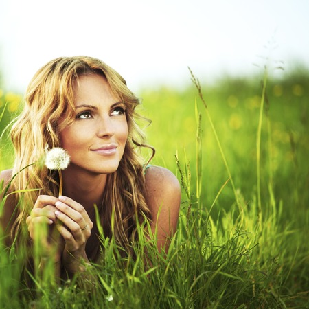Young woman with dandelion lying on grass Фото со стока - 25758575