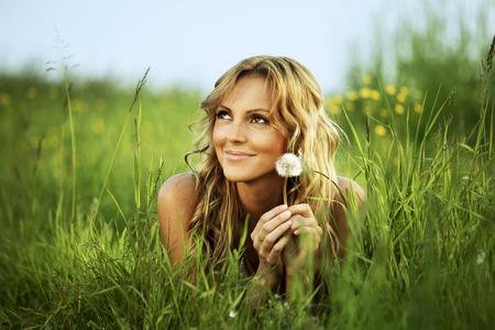 タンポポの芝生の上に横たわって若い女性 写真素材