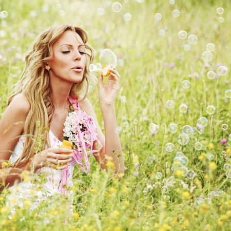 Woman blows soap bubbles on flower field photo
