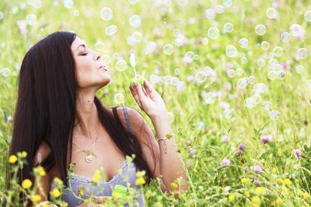 Woman blows soap bubbles on flower field photo