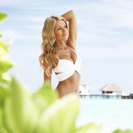 Sexy Frau im Bikini am Strand am Meer und Villa Hintergrund