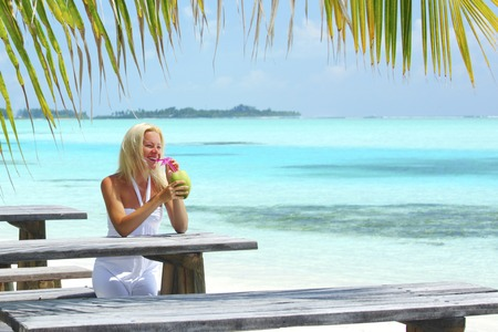 Woman drinking cocktail in tropical cafe on sea background photo