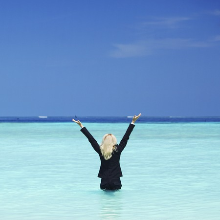 Happy business woman standing in sea waves photo