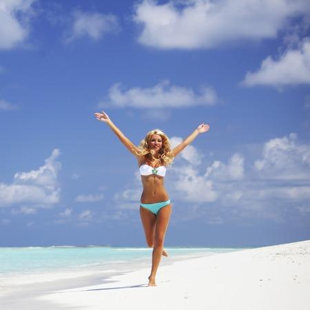ビキニ ビーチで実行されている幸せな美しい女性