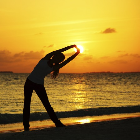 yoga sunset: Yoga woman in serene sunset at beach doing stretching workout