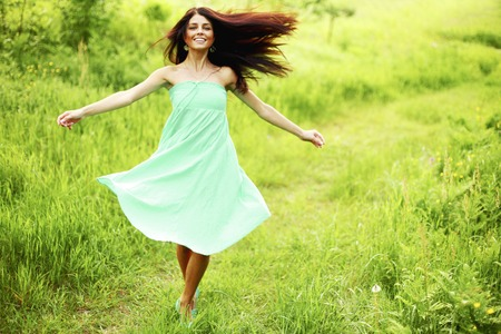 Beautiful happy young woman running on meadow Фото со стока