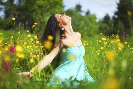 美しい若い女性は花のフィールドに自由を楽しんで