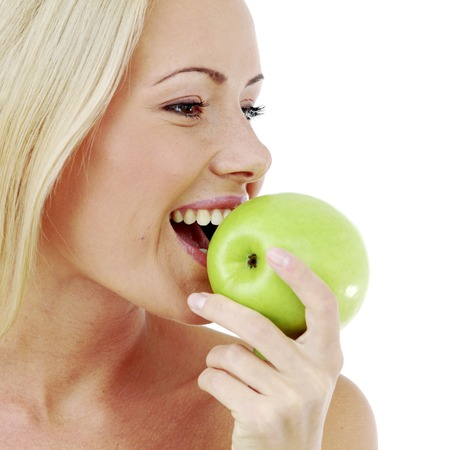 Beautiful  young woman bites a green apple, isolated on white photo