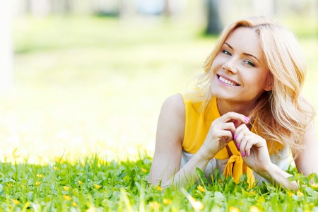 Blonde woman laying on the grass and smiling photo