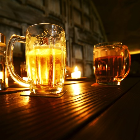 Mugs of beer in dark bar close-up photo