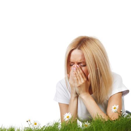Pollenallergie, vrouw niezen in een veld van bloemen