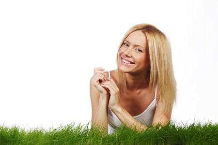 Woman laying on grass, isolated on white background photo
