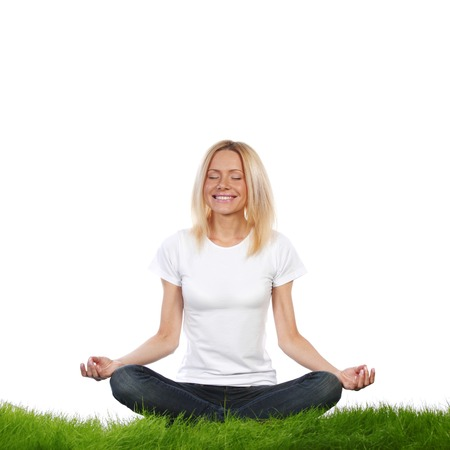 Woman in lotus position sitting on grass, studio isolated on white background photo