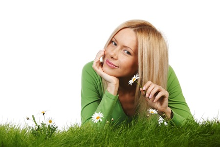 Young beautiful woman laying on daisy flowers field isolated on white background photo