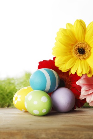 Colourful traditional Easter eggs arranged with colourful Gerbera daisies photo