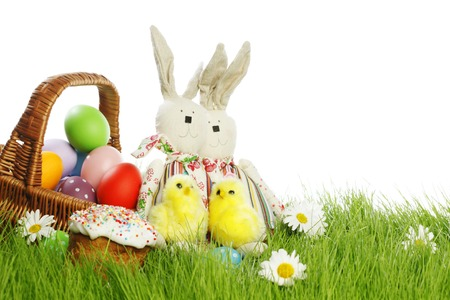 Easter card with eggs in basket and toy rabbits on green grass photo