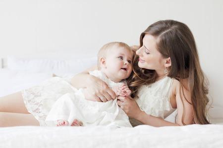 美しい母と赤ちゃんがベッドで横になっています。