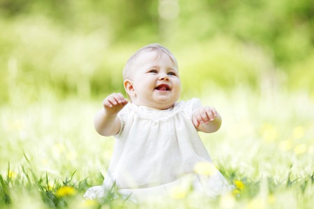 Adorable baby girl sitting on grass in park at sunny day photo