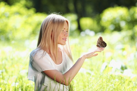 Beautiful young happy Woman playing with butterfly outdoors photo