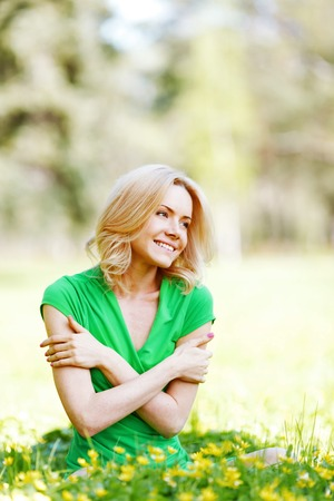 Beautiful young blond woman sitting on grass in park and enjoyng flowers photo