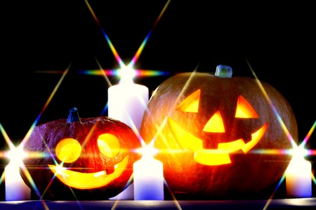 Funny Halloween pumpkins and burning candles on black background photo