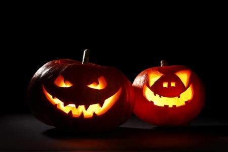 Two carved Halloween pumpkins jack-o-lantern on dark background photo