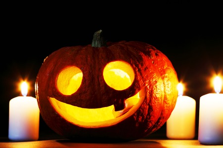 funny halloween pumpkin and burning candles on black photo