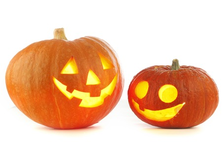 Two Jack O Lantern halloween pumpkins with candle light inside isolated on white background photo