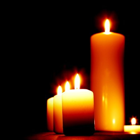 lighting background: Set of lighting candles in a row on dark background Stock Photo