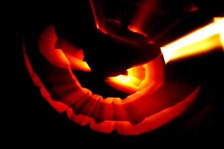 Glowing Halloween pumpkin with rays of light on black background photo