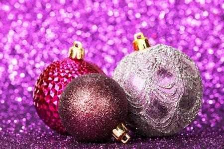 Beautiful purple christmas balls on abstract glitter background close-up photo