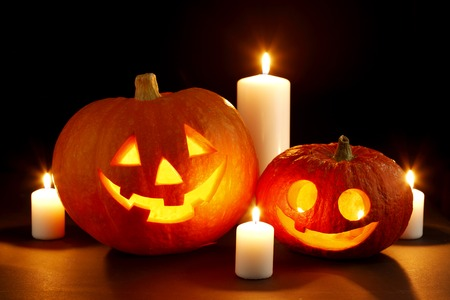 carved pumpkin: Halloween pumpkins surrounded with candles isolated on black background Stock Photo