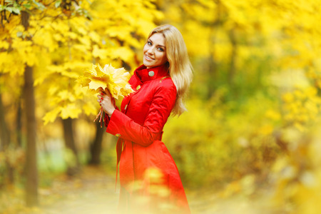 Young woman holding a bunch of autumn leaves photo