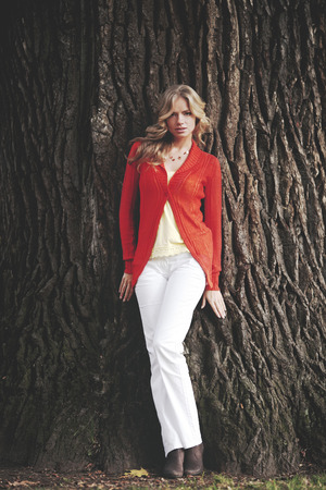 Beautiful blond woman posing on tree trunk background photo