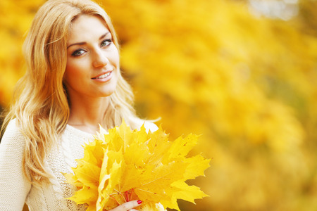 autumn in the park: Portrait of a beautiful smiling woman in the autumn park Stock Photo