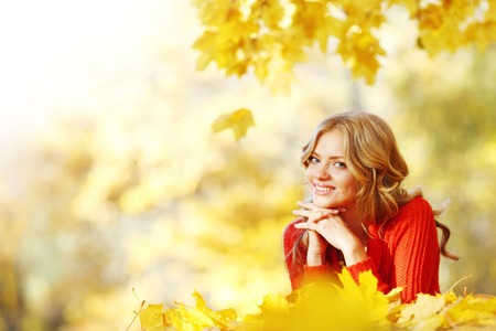 Cheerful young woman laying down on the ground covered with dry autumnal foliage in beautiful park photo