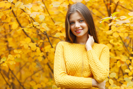 Portrait of a beautiful young woman over autumn tree background photo
