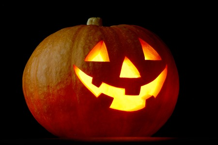 Illuminated cute glowing halloween pumpkin on black background photo