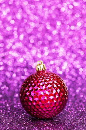 Beautiful purple christmas ball on abstract glitter background close-up photo