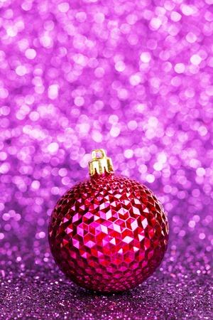 Beautiful purple christmas ball on abstract glitter background close-up photo