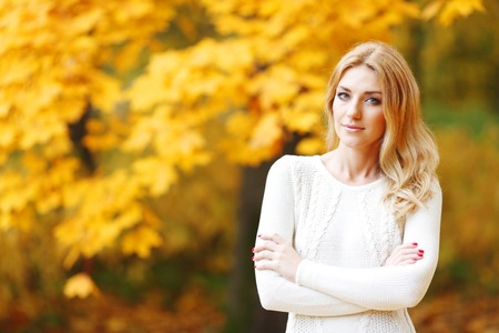 Portrait of beautiful blond woman in autumn park photo