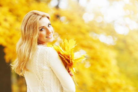 Smiling beautiful young woman with bunch of leaves in autumn park photo