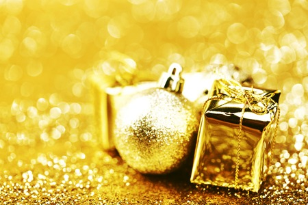 Golden Christmas ball and gifts on abstract glitter background photo