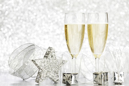 silver flute: Glasses of champagne and silver gifts on glitter background