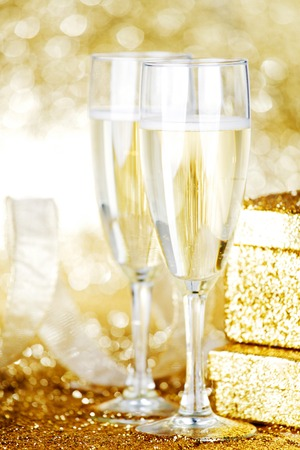 Champagne in glasses and gift box on golden background with twinkle lights photo