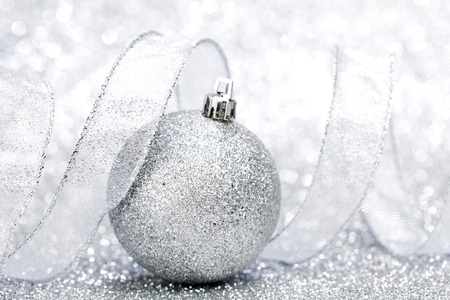 Christmas decorative ball and ribbon on silver glitter background photo
